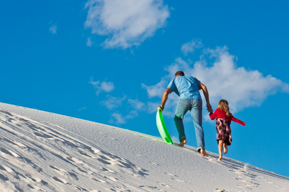 A man and a young girl, holding hands, climb up a sand dune barefoot with a green plastic sled in hand.