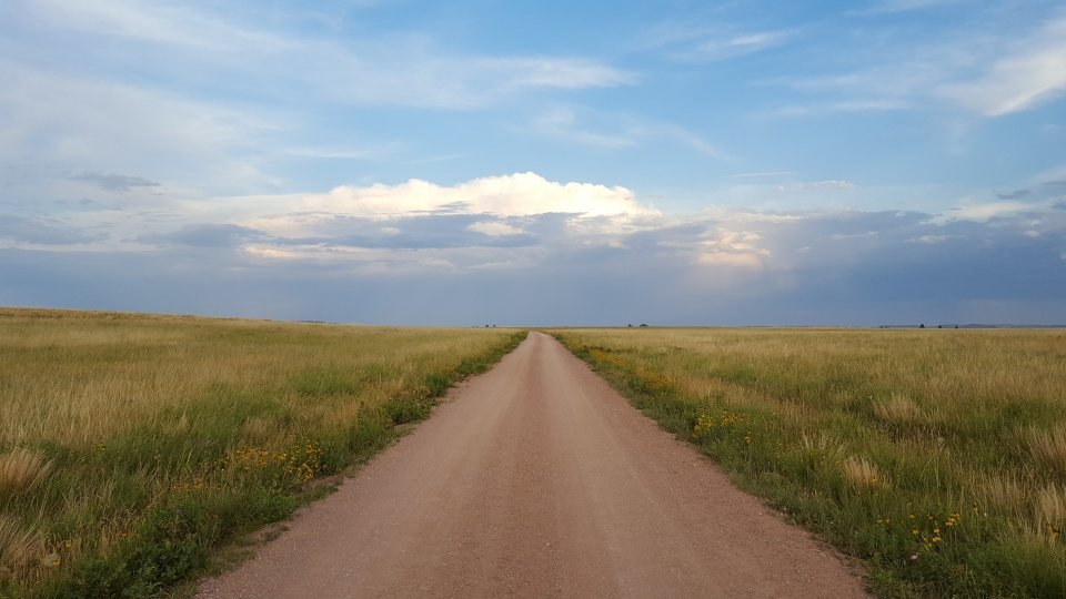 A gravel road extends through the prairie and off into the horizon