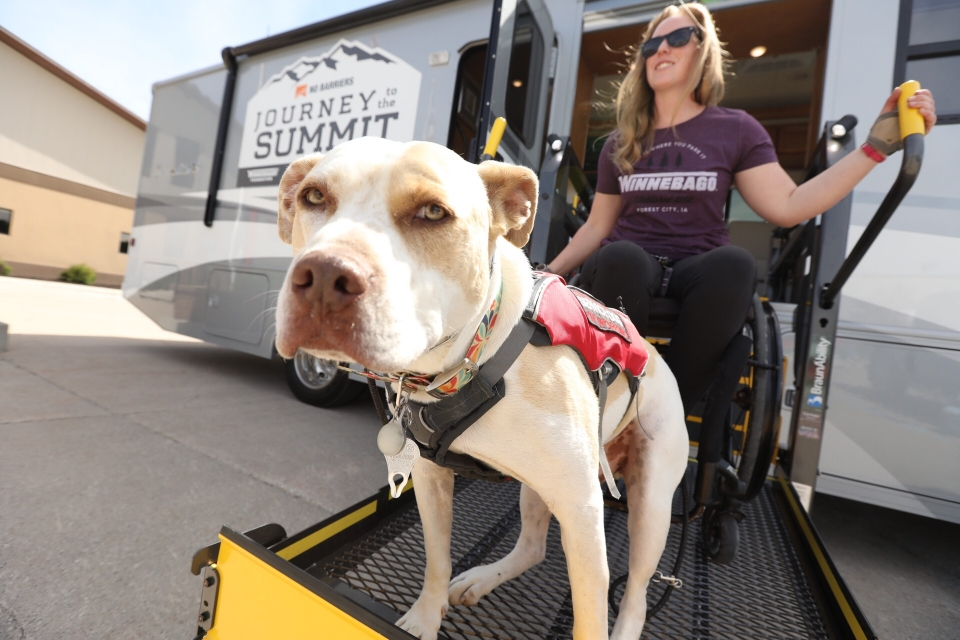 Nerissa Cannon and service dog Cash on wheelchair lift
