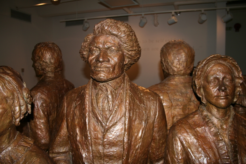 Bronze statue of Frederick Douglass, surrounded by other bronze statues of early women's rights advocates; Women's Rights National Historical Park