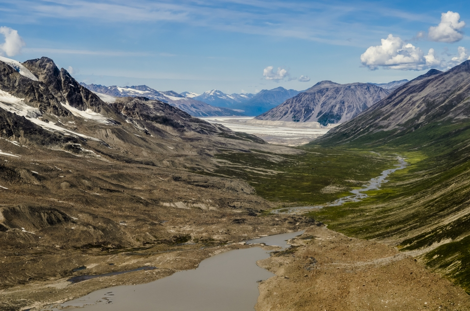 Vast landscape of a valley in between green, brown, and grey mountains at Wrengell St. Elias National Park and Preserve