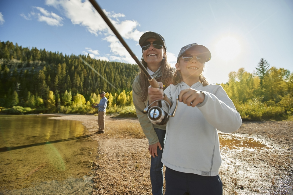 Two smiling people fish into the distance, with sunglasses on. In the background, another person casts a line into the water to fish.