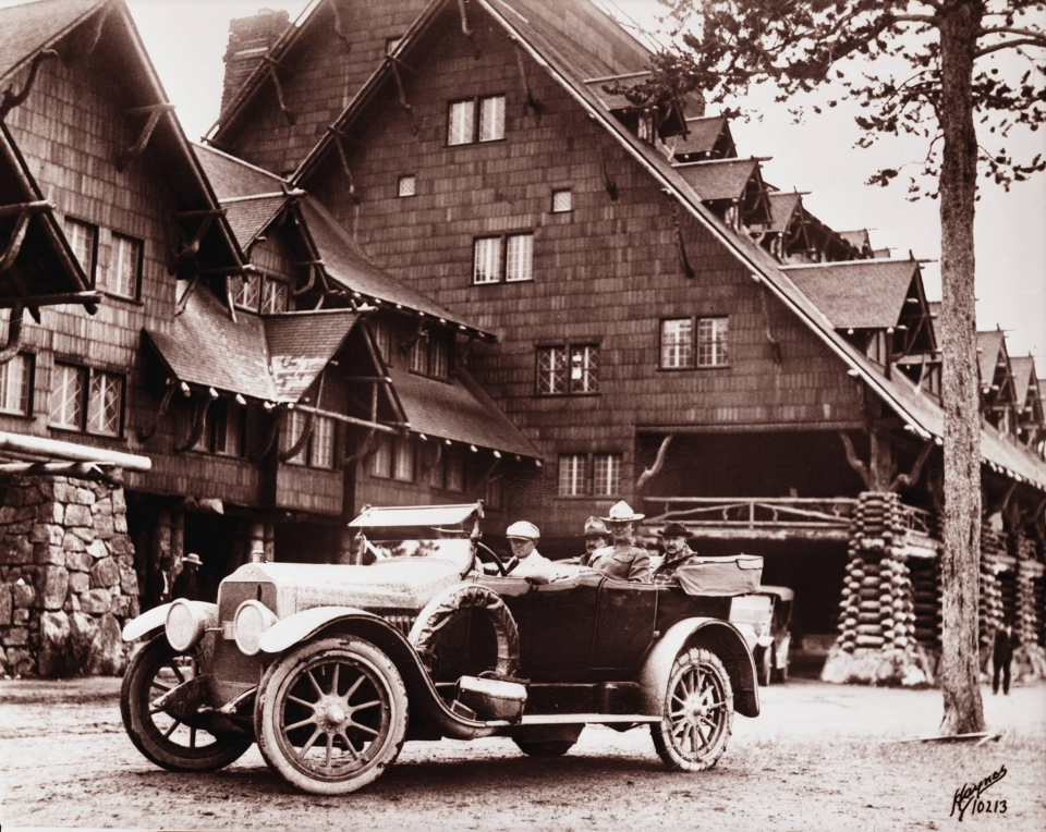 Sepia toned image of an old car in front of Old Faithful Inn