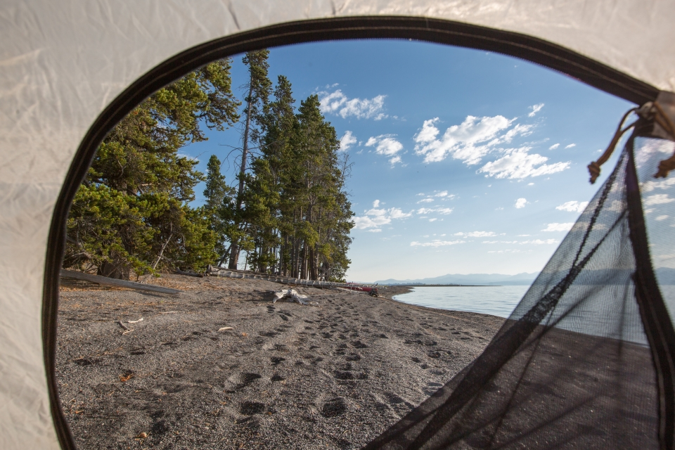 Looking out of an unzipped tent door to a beach on Yellowstone Lake