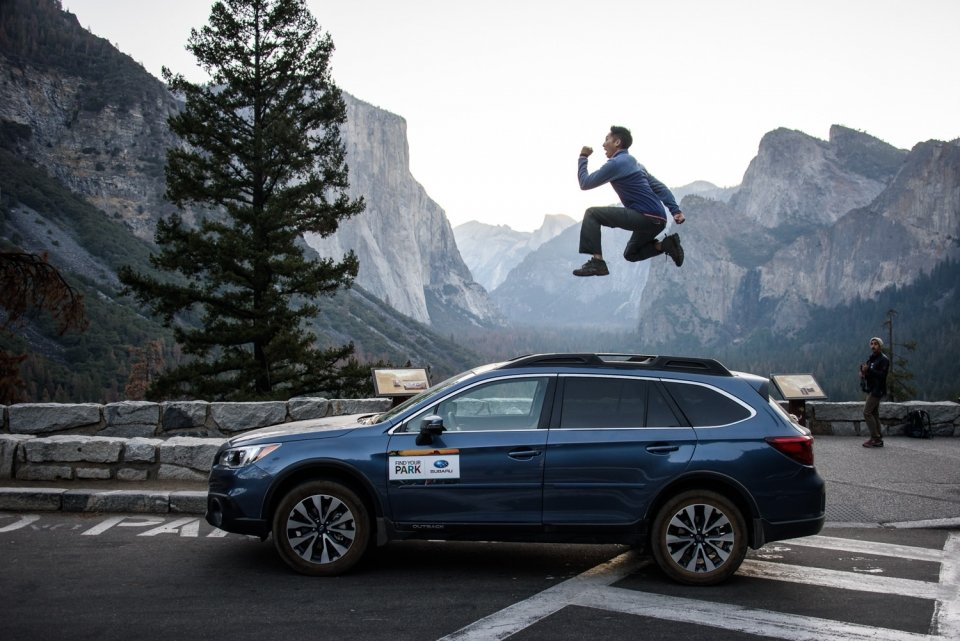 A man jumps with joy against the backdrop of a Subaru and Yosemite National Park's Tunnel View