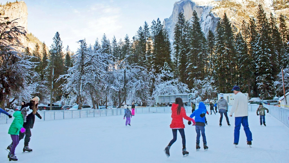 People ice skating in a risk with a snowy Half Dome in the back at Yosemite National Park