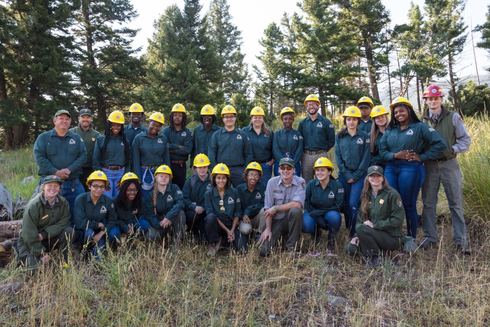 A large group of young adults part of the Youth Conservation Corps in blue uniforms and yellow hard hats posing a group in the woods at Yosemite National Park