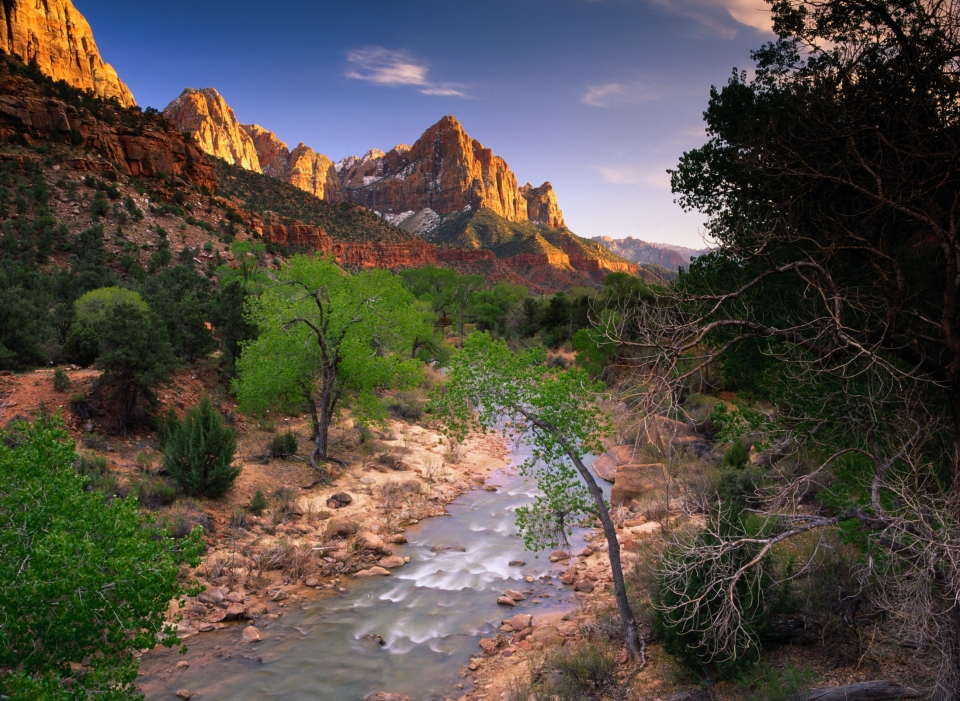 The golden sunrise hitting the orange and red sandstone cliffs with a river running through a valley at Zion National Park