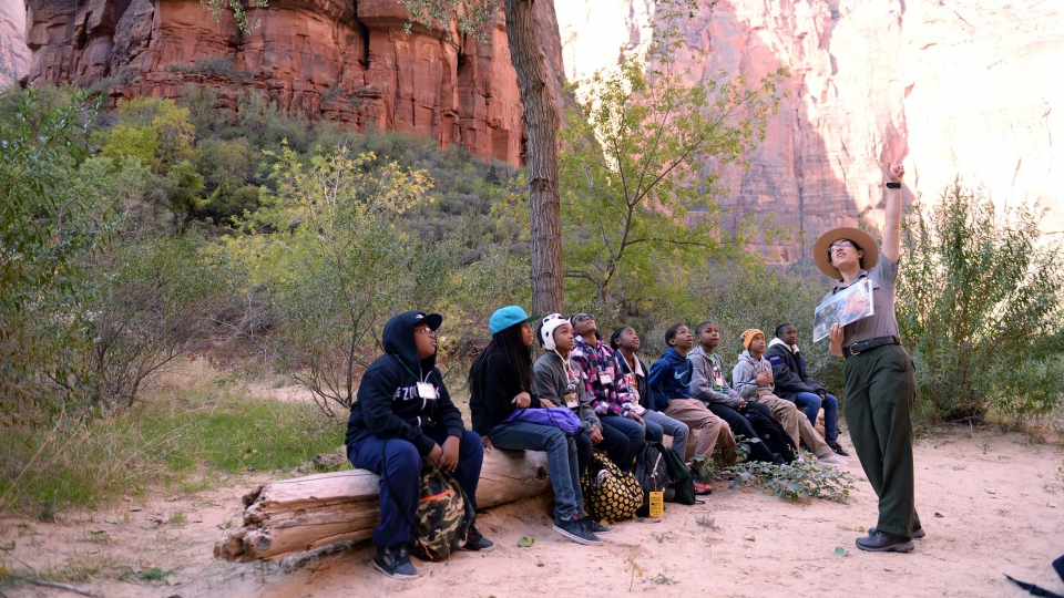 Students sit on a log opposite of a ranger pointed up at large red cliffs