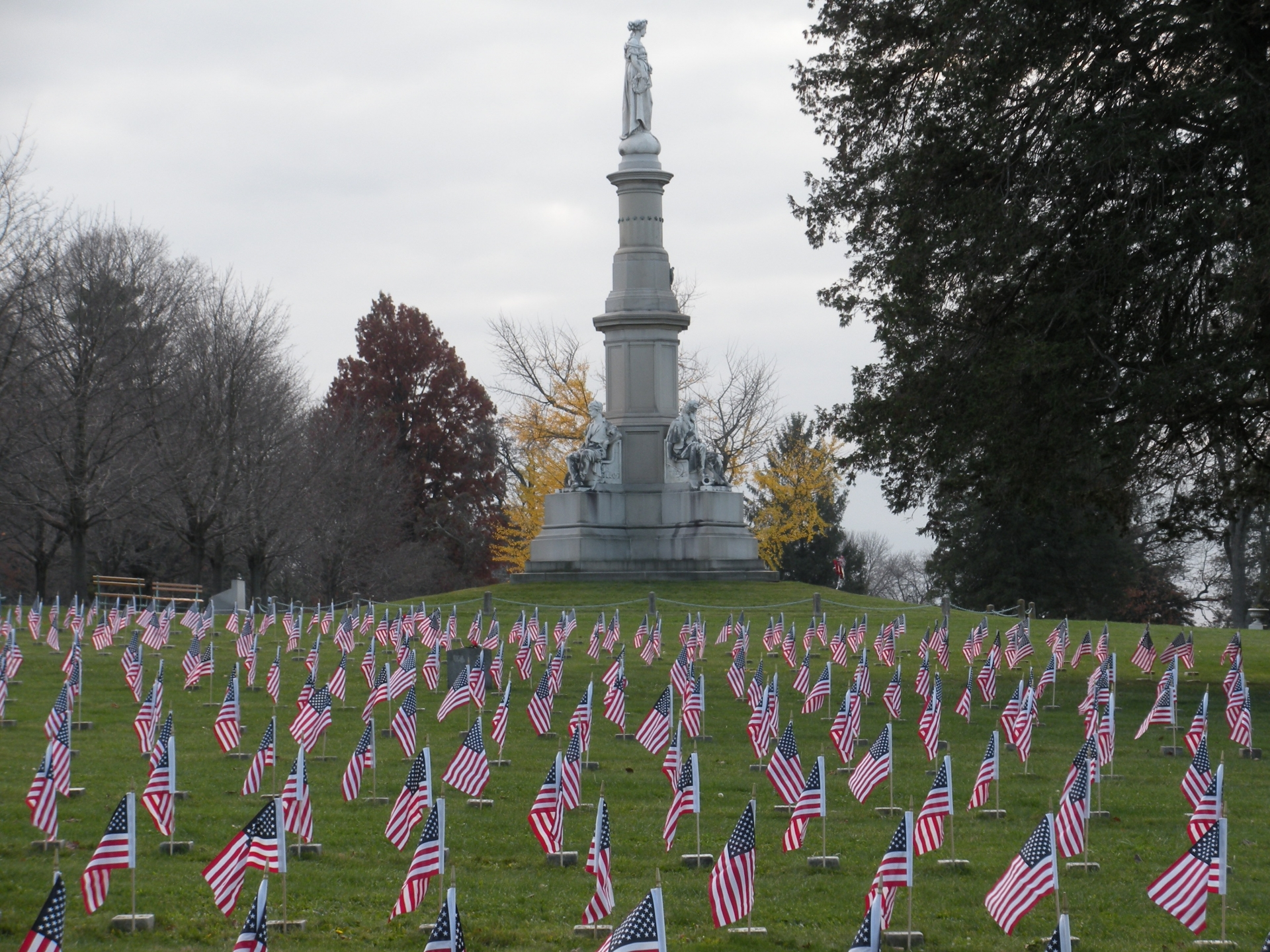 Hundreds of small American Flags, one for each grave at the base of an elaborate memorial pillar