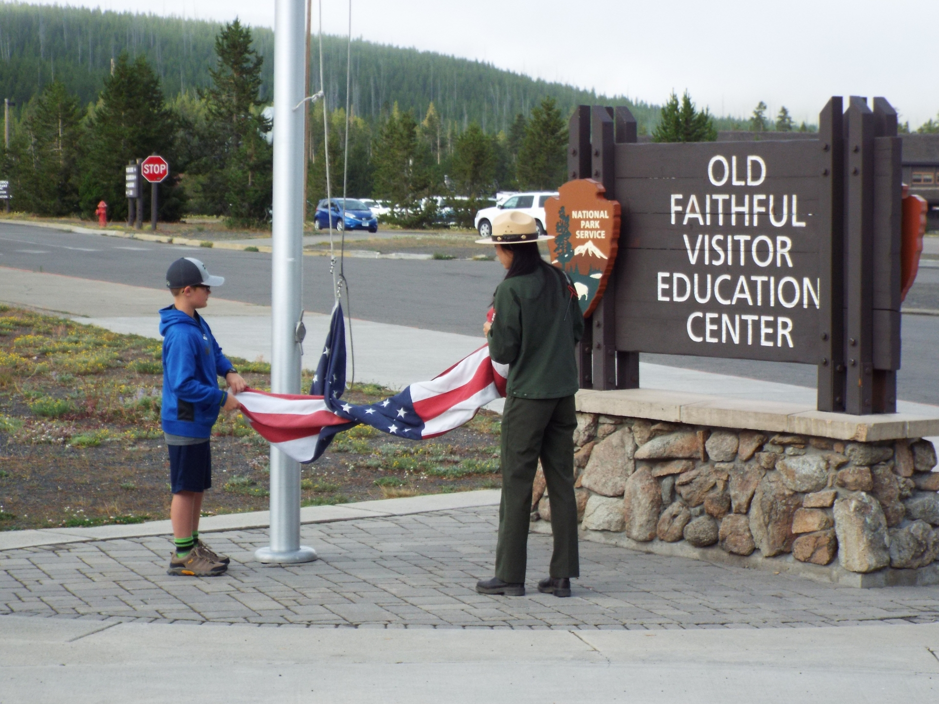 Boy Scout helps raise the flag at Old Faithful