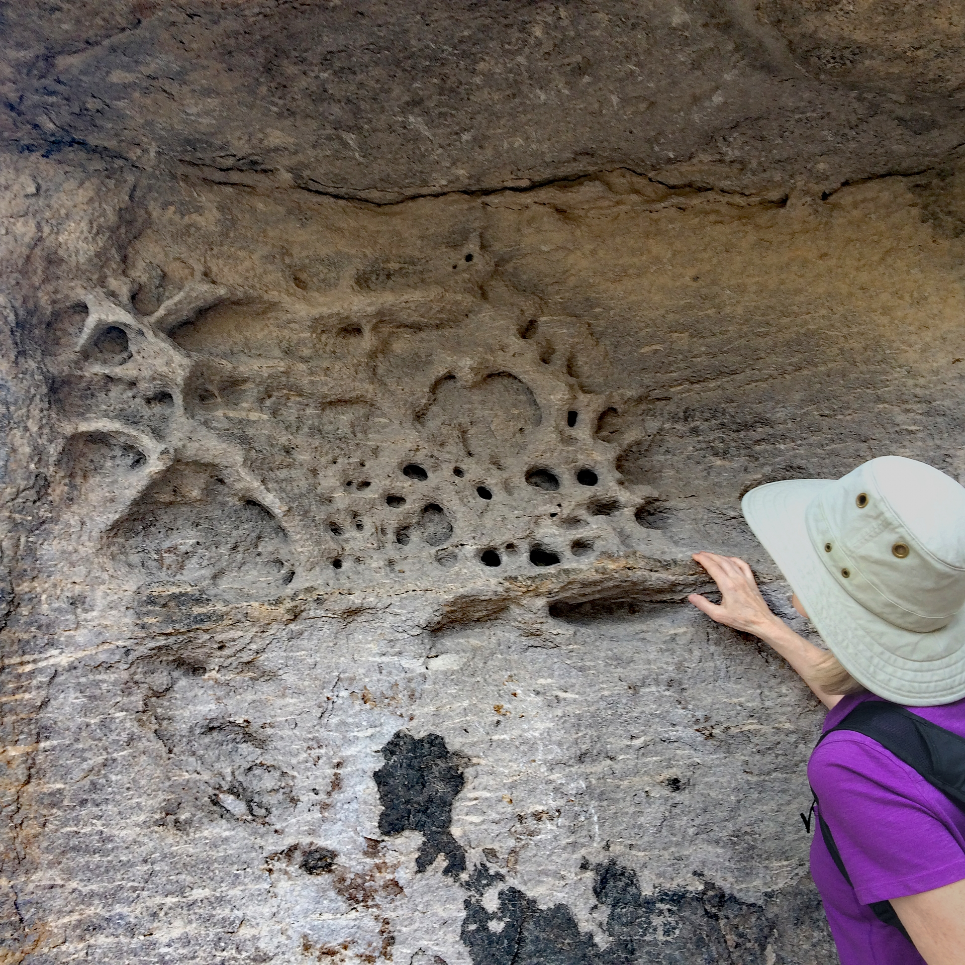 Woman looking at a close-up eroded rock formation