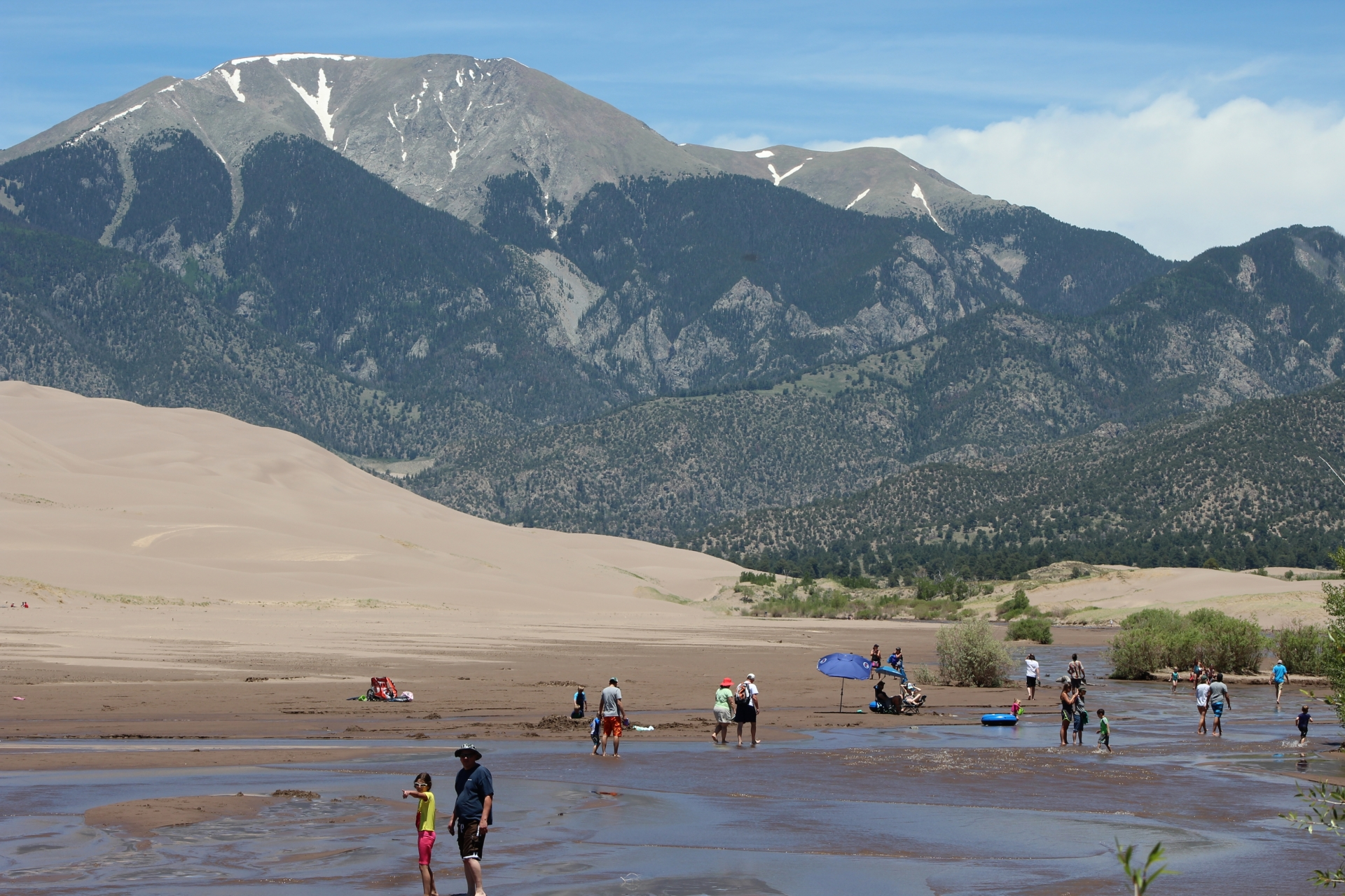 Surprisng river in the middle of a 600 ft sand dune at the base of a snow capped mountain in Colorado.  Wild escape for youngers and olders !!