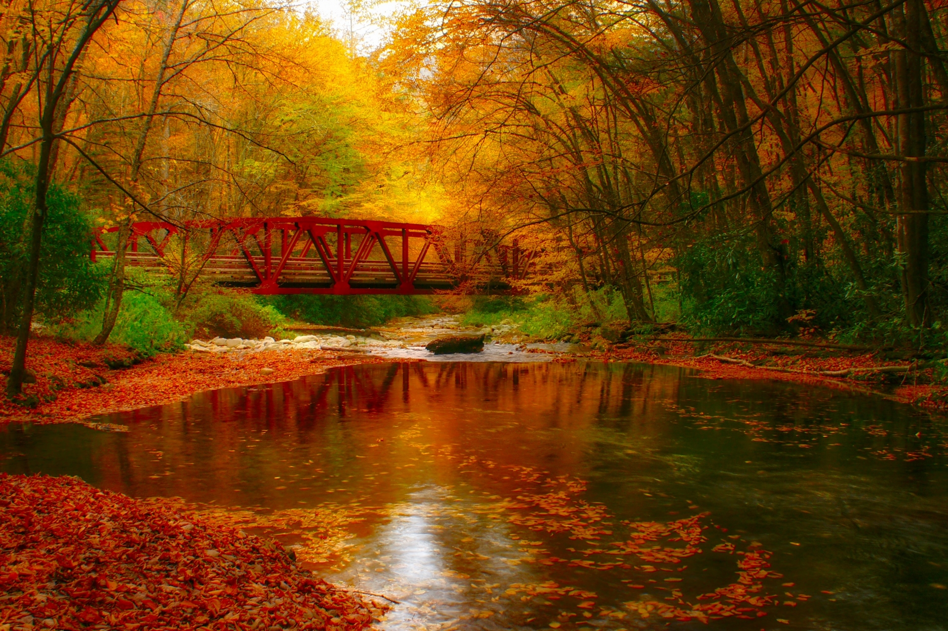 The bright red bridge crossing the Oconaluftee River inside The Great Smoky Mountains National Park.