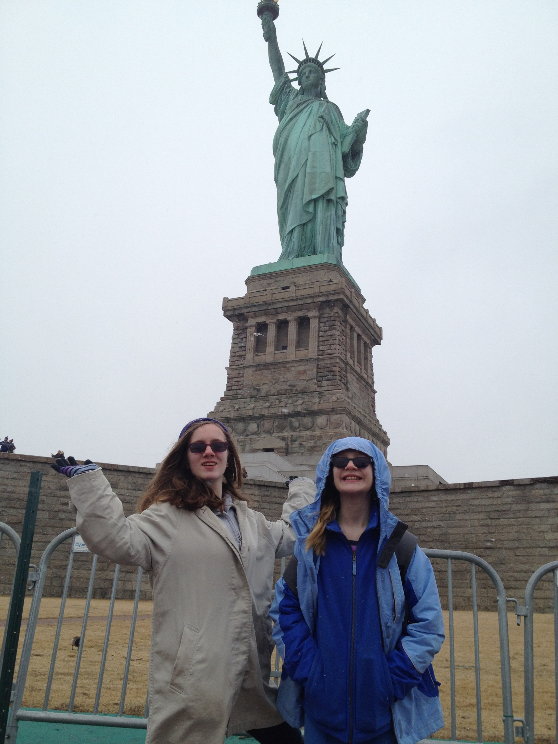 Two girls in coats standing in front of the statue of liberty in New York.