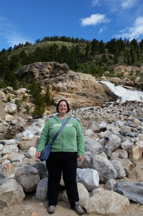 Woman standing at foot of Alluvial Fan waterfall