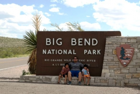 "Family posing at entrance sign to Big Bend National Park. Sign reads, ""Big Bend National Park, Rio Grande Wild Scenic River"""