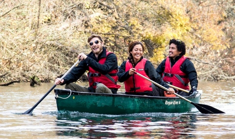 Group of 3 canoeing on a river.