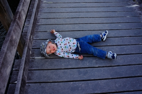Toddler laying on boardwalk