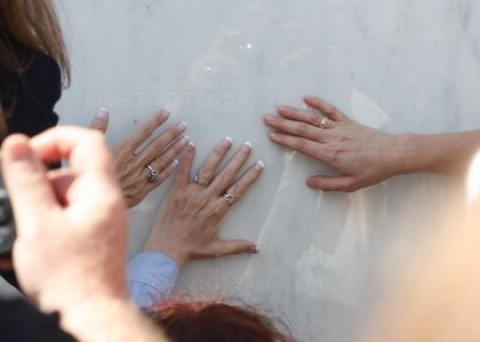 Visitors to the Flight 93 National Memorial placing hands on memorial wall