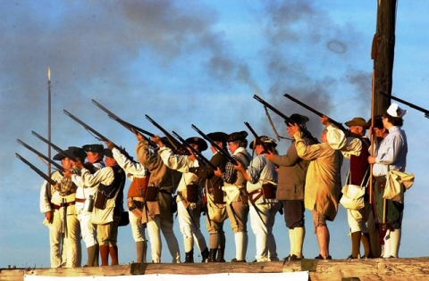 Living historians reenact the American Revolution with guns during a special two-day event at Fort Stanwix National Monument in New York