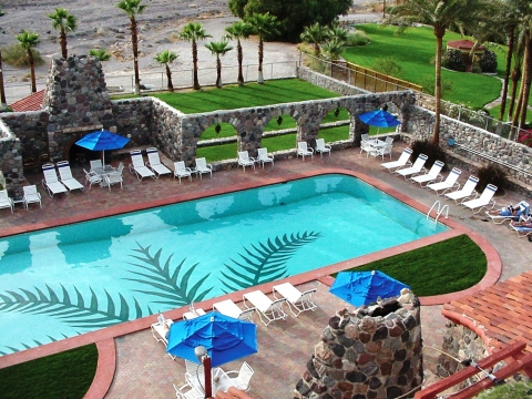 Blue waters of a tiled pool, surrounded by lounge chairs at the Inn at Furnace Creek. The Inn and the Ranch at Furnace Creek feature flow-through pools naturally fed by warm springs that keep the pools' temperature at a comfortable 82 degrees