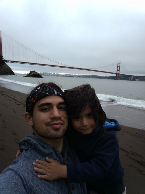 A man and a child on a beach at Kirby Cove with a foggy Golden Gate Bridge in the back