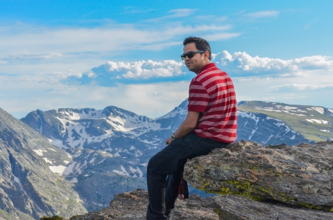 Photographer Manish Mamtani sitting on an overlook at the Rocky Mountains