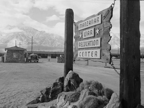 Manzanar War Relocation Center sign on a wooden board. Mountains in the background.