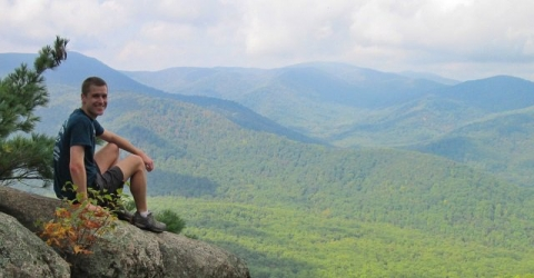 Mikah Meyer sitting on during a hike, overlooking a valley of green forest