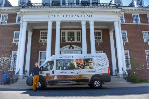 Mikah standing with a candle delivery truck in front of Louis J. Boland Hall