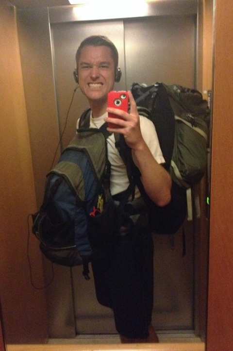 Mikah Meyer, during his travels, wearing a backpack, taking a selfie in an elevator mirror