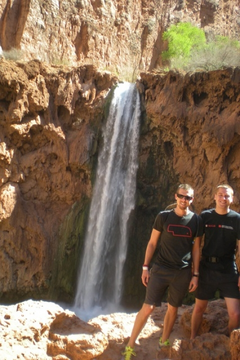 Mikah Meyer and friend posing for a picture in front of a waterfall at the Grand Canyon