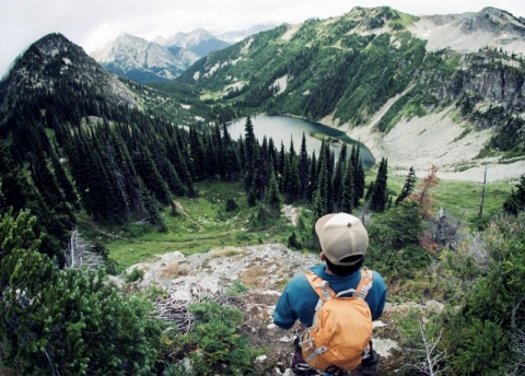 Boy looking down from mountain on North Cascades National Park, with pine trees, streams and mountains