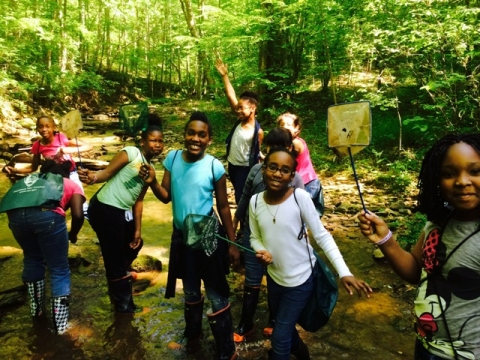 Students playing in park stream, participating in Open OutDoors for Kids. program.