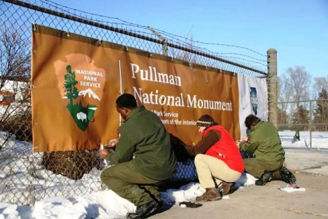 "Three people putting sign on fence that reads, ""National Park Service, Pullman National Monument, National Park Service, Department of the Interior"""