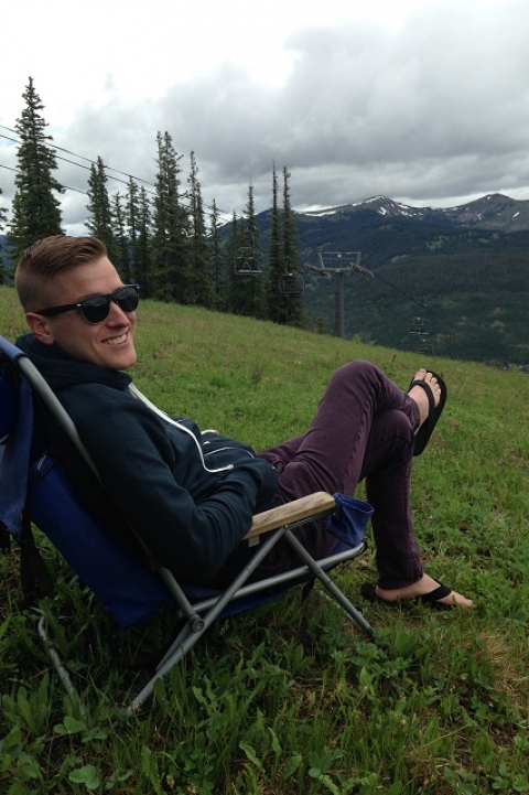 Mikah lounging on chair looking outward on snow capped mountains