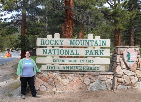 "Woman poses in front of sign, ""Rocky Mountain National Park, Established in 1915, 100th Anniversary"""