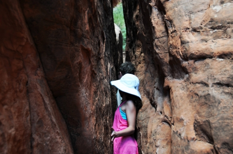 People squeezing through rocks on a Fiery Furnace hike at Arches National Park.