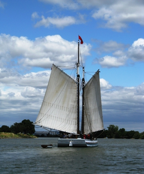 Large sailboat on water beneath clouds