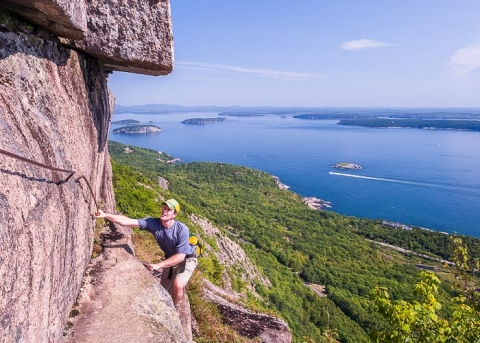 Man climbing up cliff on Champlain Mountain at Acadia National Park