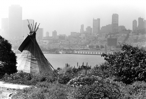 Black and white photo of teepee on Alcatraz with skyline of San Francisco in the background