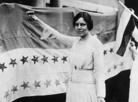 Black and white image of Alice Paul raising a glass in front of the ratification banner