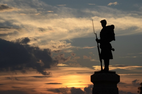 Civil war solider statue is backlit by an orange and yellow sunset