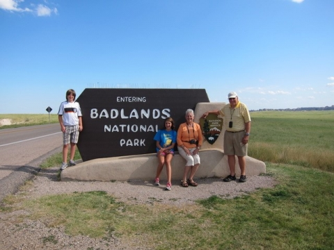 A family of four poses in front of the Badlands National Park entrance sign