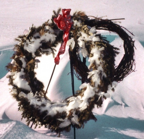Wreath with red bow covered in snow
