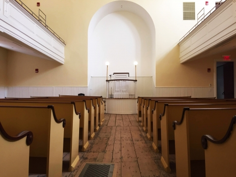 Wooden benches facing a raised platform; African Meeting House at Boston African American National Historic Site