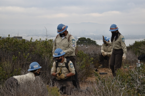 A group of service corps members, each in a hard hat and face mask