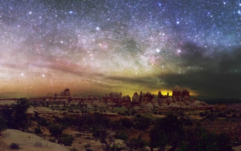 The colorful yellow, pinks, blues, and purples of the night sky over Canyonlands National Park