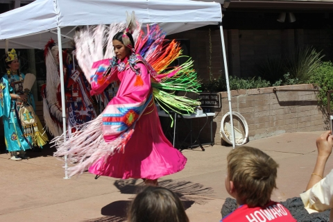 Native American dressed in a neon pink dress spinning during a performance at Capulin Volcano National Monument